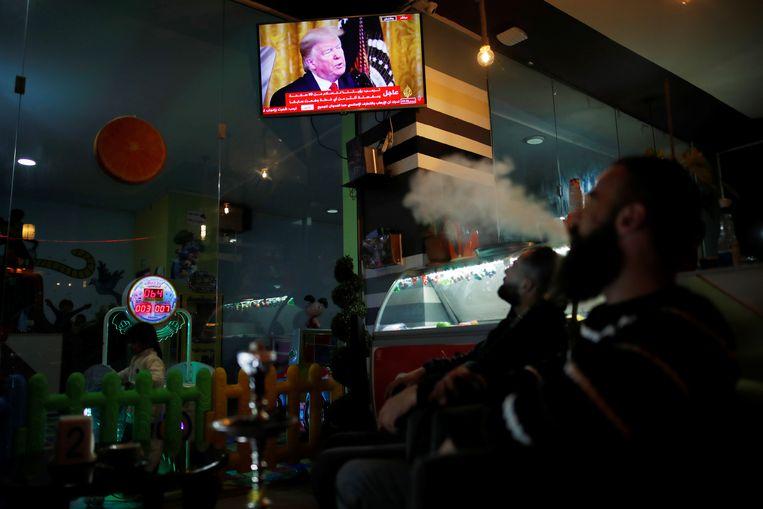 Palestijnen bekijken de aankondiging van Amerikaans president Trump in een koffiebar in Abu Dis. Beeld REUTERS
