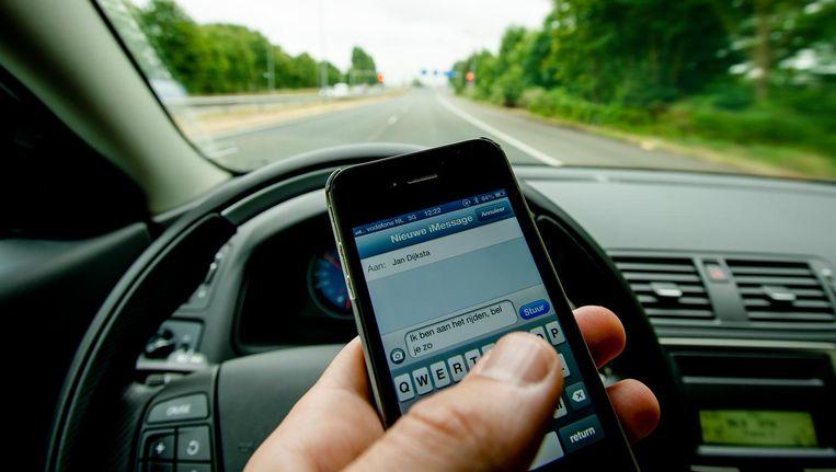 Het aantal boetes voor automobilisten die een telefoon vasthouden, is spectaculair gegroeid. Beeld ANP