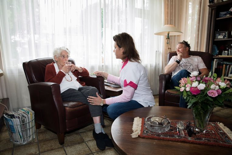 Kitty van der Ark krijgt hulp bij het drinken van verpleegkundige Michelle Leijendekkers. Haar zoon Bob komt als mantelzorger twee tot drie keer per week langs. Beeld Inge van Mill