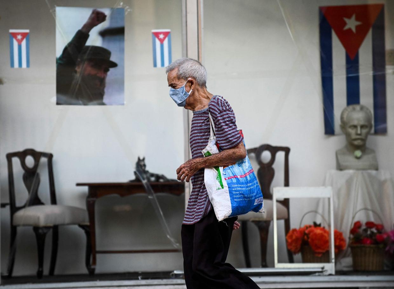 Een Cubaan loopt voorbij een poster van wijlen Fidel Castro in Havana. Beeld AFP