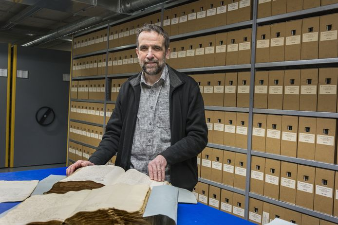 Gerard Kuijpers in het magazijn van het RHCE, waar vele duizenden oude documenten zijn opgeslagen