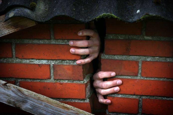 Handen zijn zichtbaar door een scheur in de muur van een woning in Groningen.