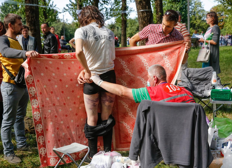 Artsen behandelen in de open lucht verwondingen van inwoners van Minsk die waren opgepakt door de oproerpolitie en in de gevangenis werden geslagen. Beeld EPA