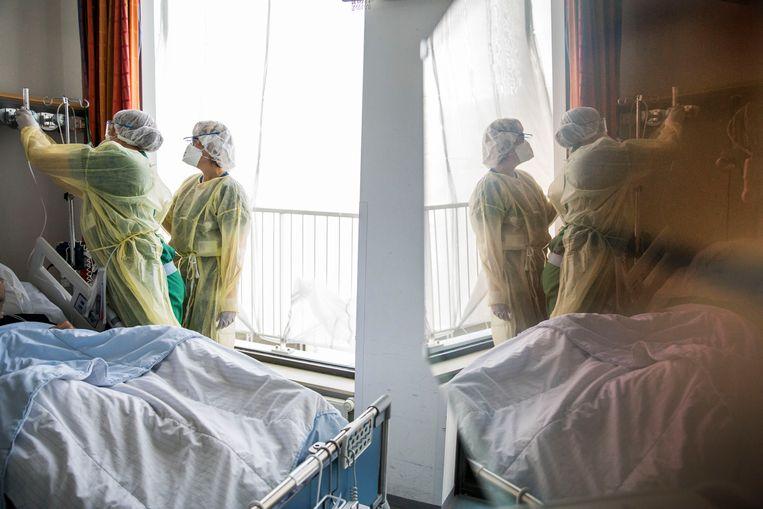 Artsen en verpleegkundige in beschermende pakken op de afdeling waar corona patiënten liggen. Beeld Arie Kievit