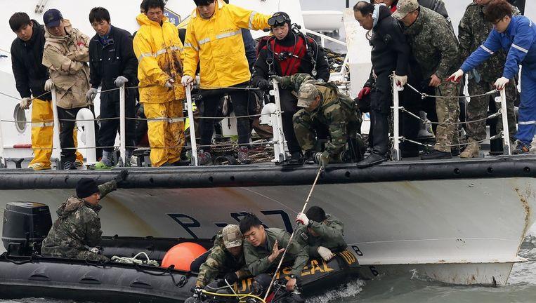 Een Zuid-Koreaans marineteam hijst een van zijn kikvorsmannen omhoog tijdens voorbereidingen voor de berging van de gezonken veerboot. Beeld epa