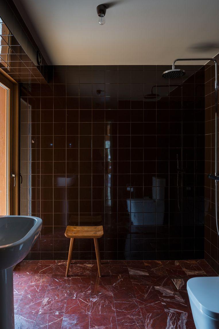 De vloer van de badkamer is gemaakt van Italiaans Red Jasper-marmer, de wandtegeltjes zijn van Engels keramiek.Het krukje is een ontwerp van Carl Malmsten, de wastafel van Jasper Morrison.  Beeld Nin Solis