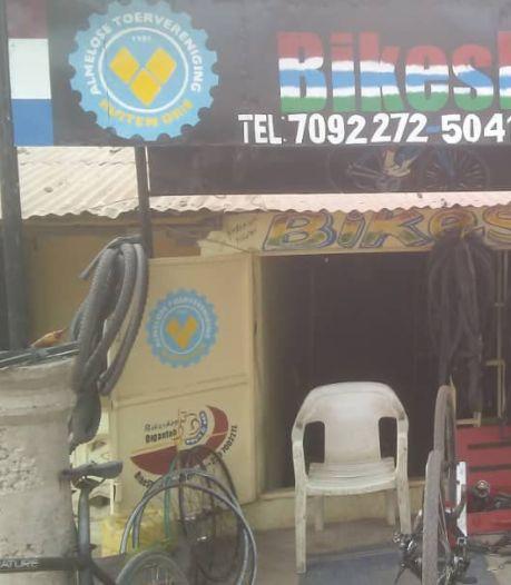 Boven deze fietsenwinkel in Gambia hangt een Almelose vlag, hoe zit dat?