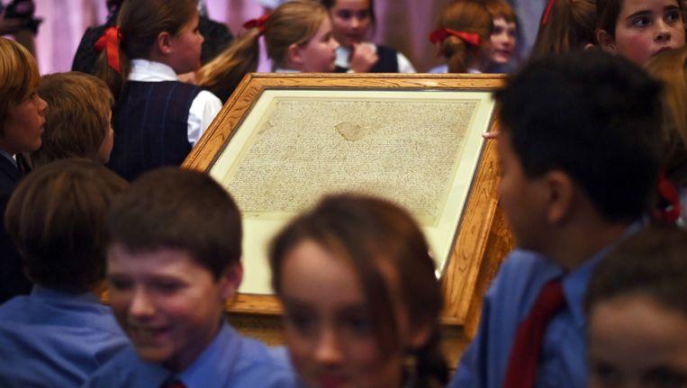 Schoolkinderen rond een kopie van de Magna Carta in het Australische Canberra. Beeld EPA