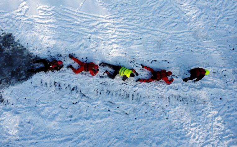 Reddingswerkers houden een oefening op het Glebokie-meer in Szczecin, in het noordwesten van Polen. Zij moeten paraat zijn als mensen onverhoopt door het ijs zakken.  Beeld EPA