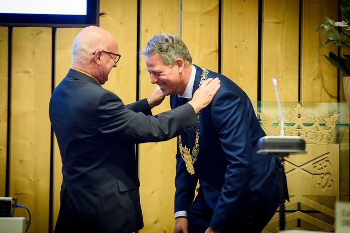 Raadslid en raadsnestor Toon van Dun hangt Remco Bosma de ambtsketen van Bladel om.