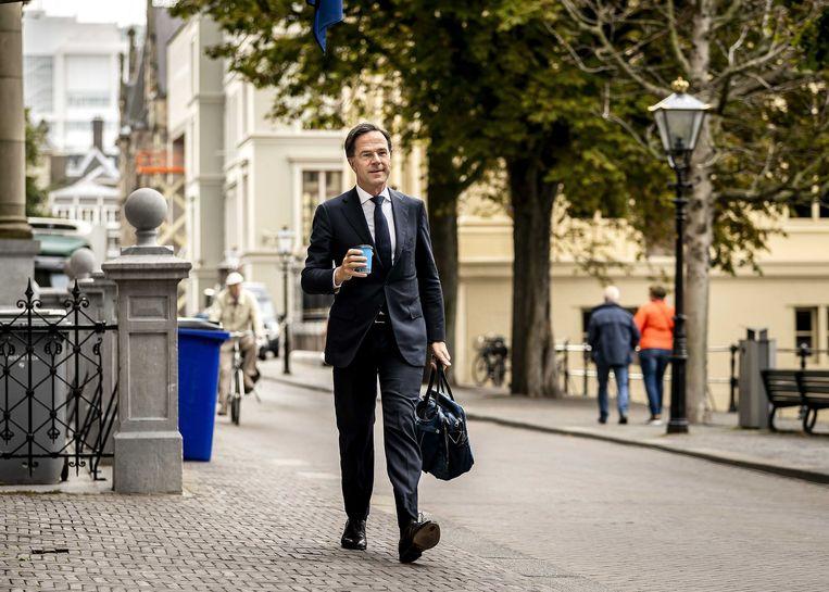 Demissionair premier Mark Rutte loopt met een kop koffie in de hand door de Haagse binnenstad nabij het Binnenhof. Beeld ANP