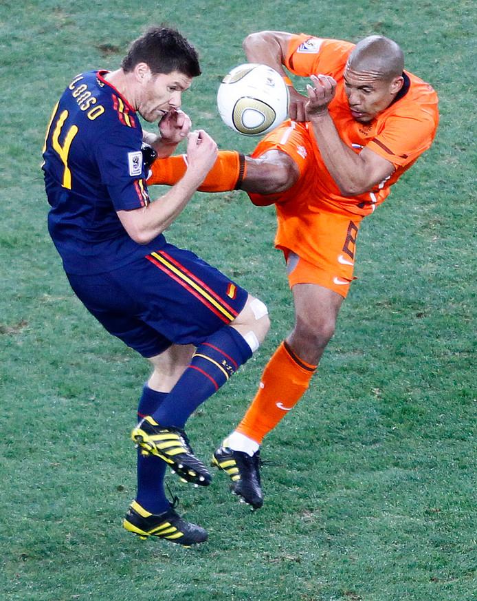 Nigel de Jong torpedeert Xabi Alonso.