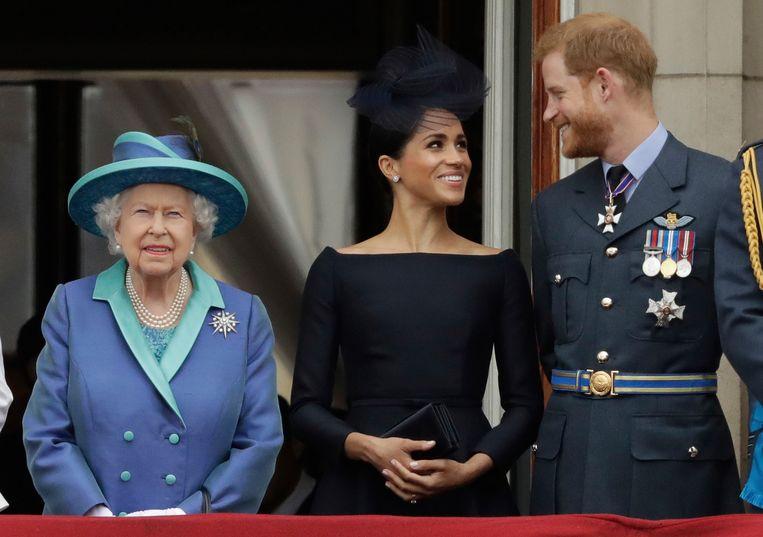Koningin Elizabeth kijkt op 10 juli 2018 met Meghan en Harry aan haar zijde op Buckingham Palace naar een overvliegende formatie van de Royal Air Force, die zijn honderdjarig bestaan viert. Beeld Matt Dunham / AP