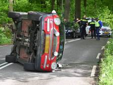 Auto belandt op z'n zij in Arnhem; boodschappen liggen op straat