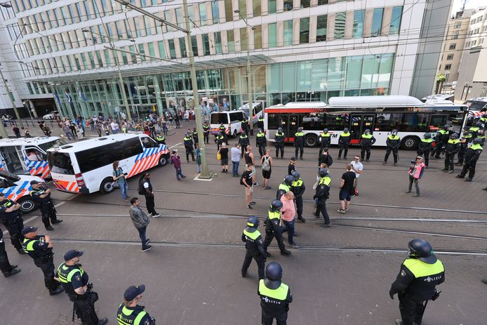 Gearresteerde mensen worden in bussen van de HTM naar een politiebureau gebracht.