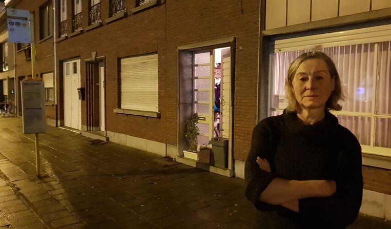 Linda Van Dooren met haar woning en de gebarricadeerde deurdorpel op de achtergrond.