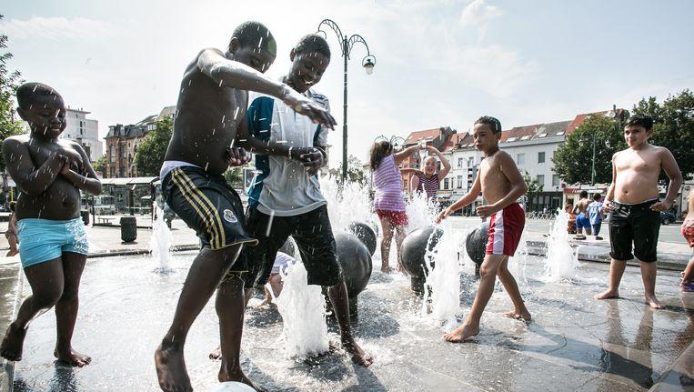 Brusselse jongeren spelen samen met voetbal in water in de warme zomerzon. Beeld Wouter Van Vooren