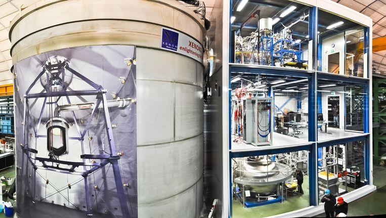 Het Xenon1T-experiment in het ondergrondse Gran Sasso laboratorium, in Italië. Links de watertank, met daarin de container vol xenon. Rechts de analyseapparatuur en het overig toebehoren van het experiment.  Beeld Xenon1T