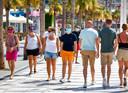 Toeristen lopen met een mondkapje over de boulevard langs het Levante strand van Benidorm aan de Costa Blanca.