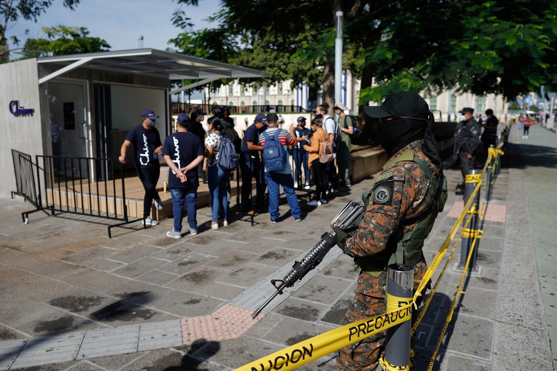Onder het toeziend oog van een gewapende bewaker drommen mensen met vragen zich rond een bitcoin-pinautomaat. Beeld Reuters