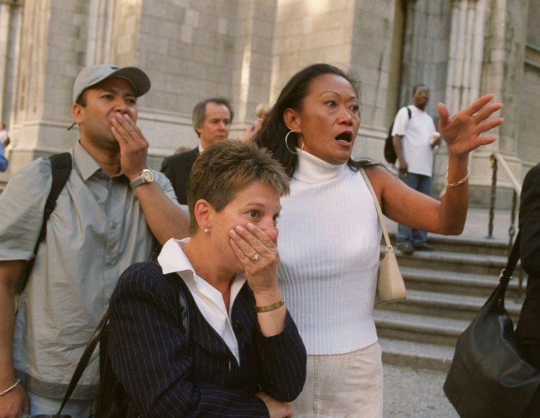 Bij St. Patrick's Cathedral aan Fifth Avenue kijken mensen geschokt naar het World Trade Center, nadat tweevliegtuigen zich in de gebouwen hebben geboord.  Beeld AP