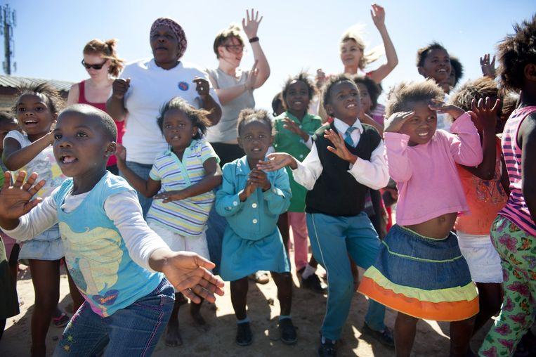 Zingen en dansen bij de Grandma's Against Poverty & Aids in township Khayelitsha bij Kaapstad, Zuid-Afrika. De oma's vangen met behulp van westerse vrijwilligers dagelijks ruim tweehonderd jonge kinderen op, zodat die niet op straat gaan rondhangen. Beeld An-Sofie Kesteleyn