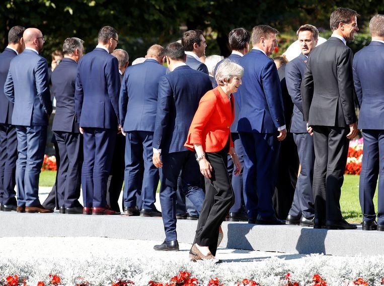 De Britse premier Theresa May zoekt haar plekje tijdens de EU-top vorige maand in Salzburg. Beeld REUTERS