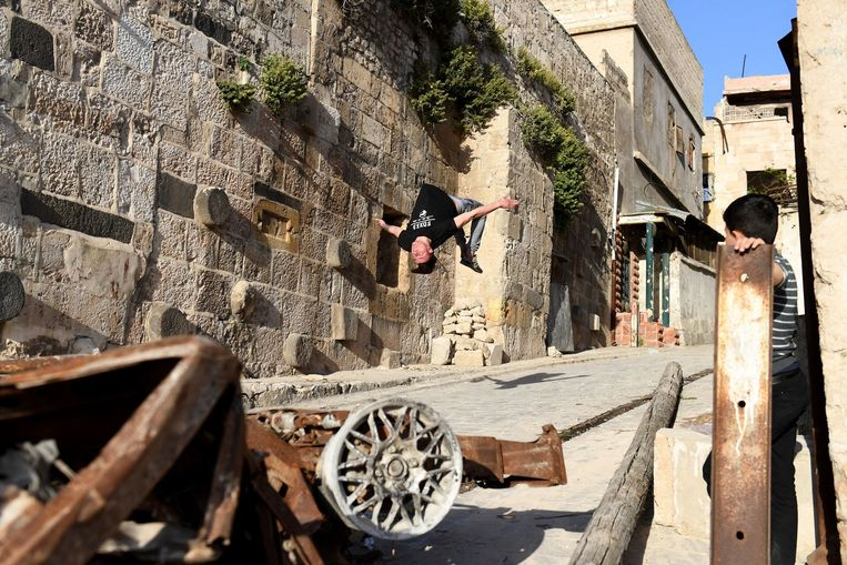 TOPSHOT - A Syrian youth practices parkour in Aleppo, northern Syria, on April 7, 2018. The government retook full control of Aleppo from rebel-fighters in December 2016. / AFP PHOTO / George OURFALIAN Beeld AFP