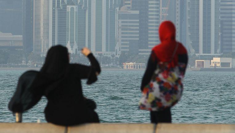 Twee vrouwen voor de skyline van Doha, de hoofdstad van Qatar. In deze stad zit Laura al drie maanden vast. Beeld © getty images