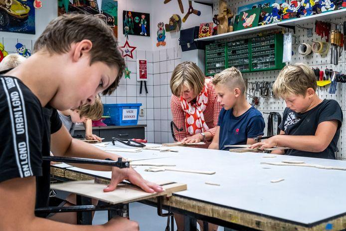 Marianne van Dooren (midden) helpt de kinderen bij hobbyclub Braakhuizen Noord met zagen.