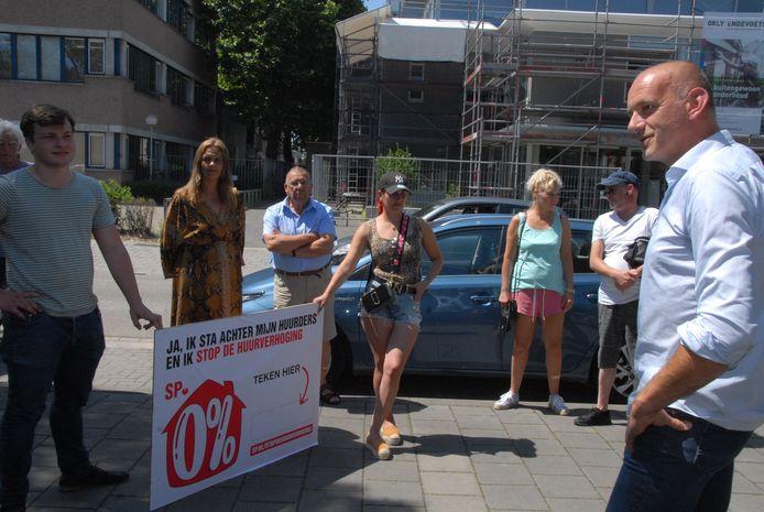 Actie van de SP tegen de aangekondigde huurverhoging bij het kantoor van Zayaz. Bram Roovers(links) en Lara Kuenen houden samen het actiebord vast, in aanwezigheid van onder meer Rob Bogaart, directeur Klant en Samenleving van BrabantWonen