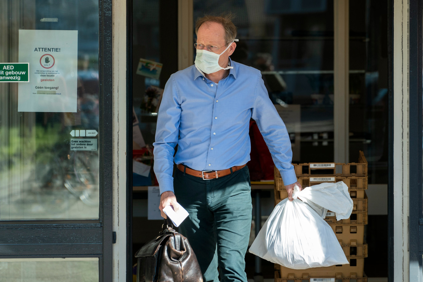 Een dokter met mondkapje verlaat een verzorgingstehuis.