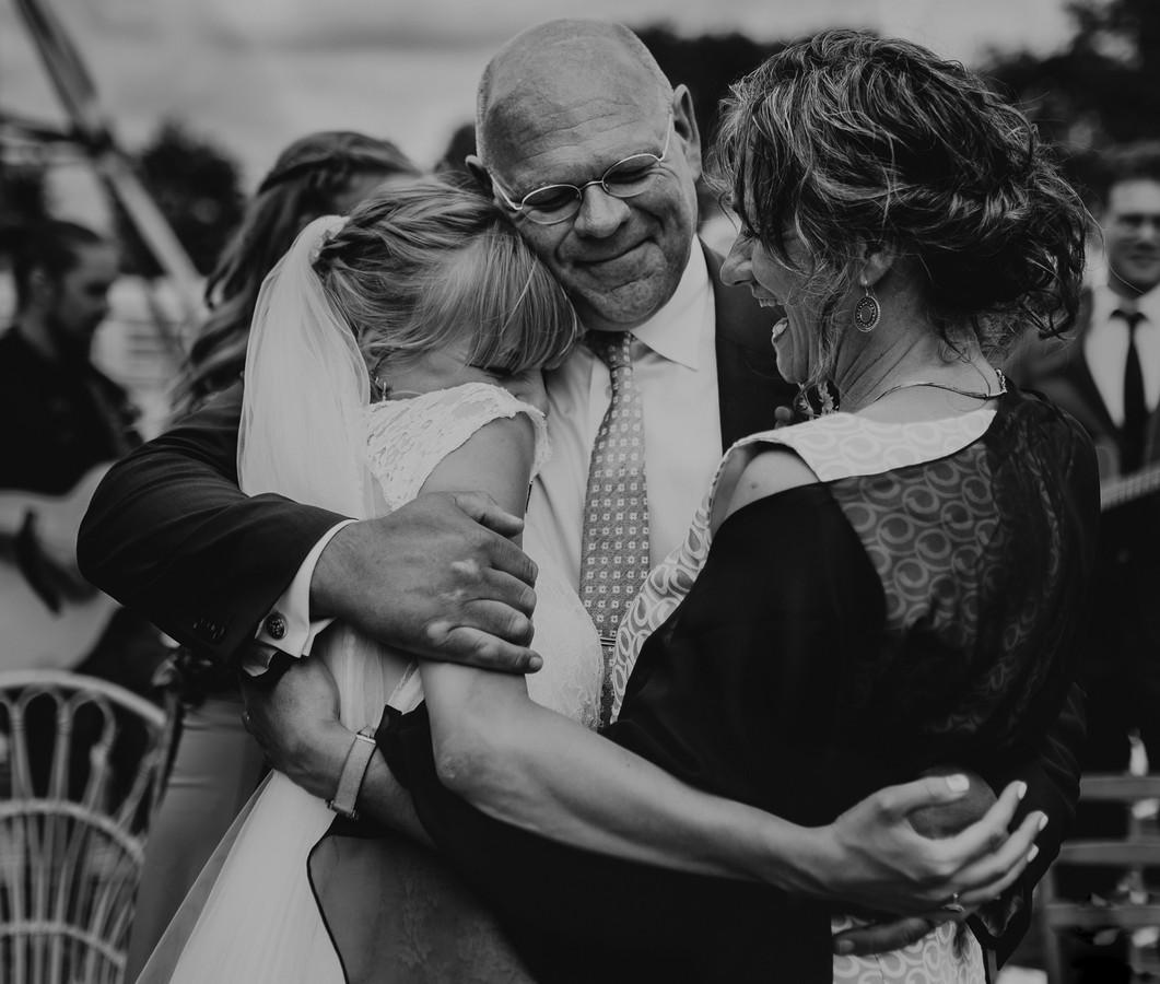 Bruid wordt door haar schoonouders liefdevol in de familie verwelkomd.