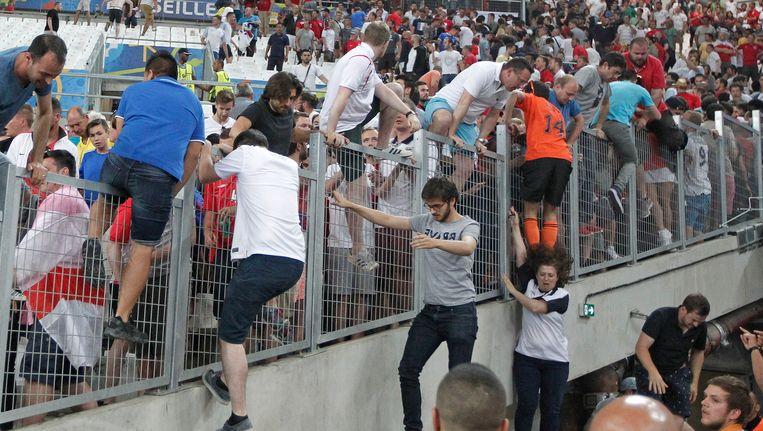 Mensen proberen de tribune te ontvluchten na rellen tussen Engelse en Russische voetbalfans. Beeld ap
