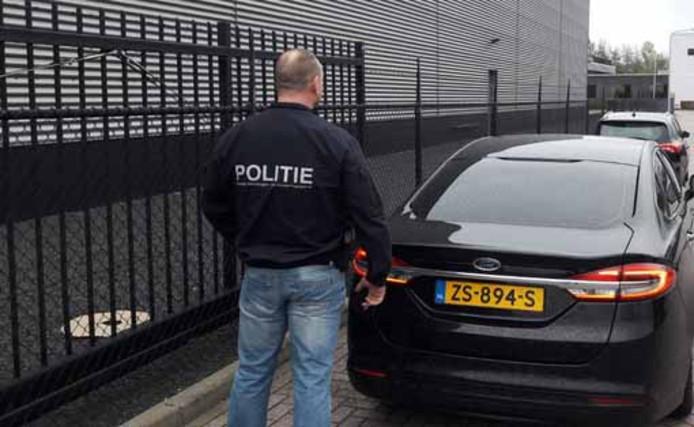 FIOD en politie hebben woensdag doorzoekingen gedaan bij tapijtbedrijven in Genemuiden. Op deze foto een politiemedewerker die net bij een van de doorzochte bedrijven, IBG Flooring, vandaan komt.