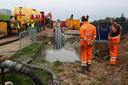 Medewerkers van de aannemers houden op het bouwterrein onder aan de dijk de mantelbuizen in het oog als ze onder de grond verdwijnen.