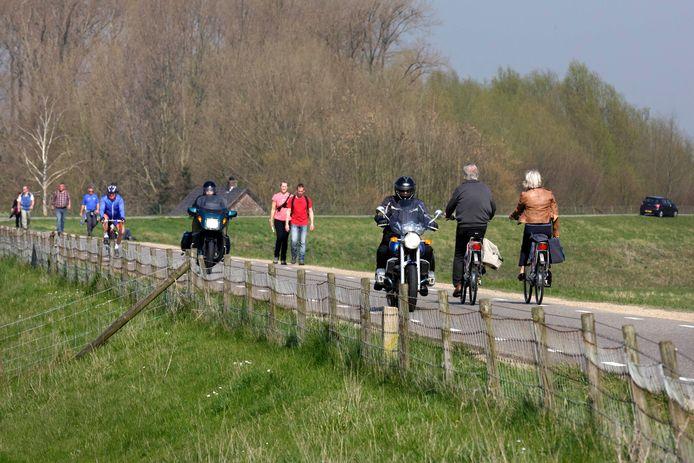 Wandelaars, fietsers en motorrijders op de dijk bij Doornenburg.