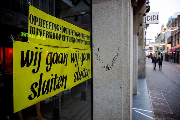 Op het raam van een gesloten winkel hangt een bord met de tekst 'Wij gaan sluiten'. Door de lockdown zijn veel niet-essentiële winkels al lange tijd gesloten en vreest de sector voor faillissementen.