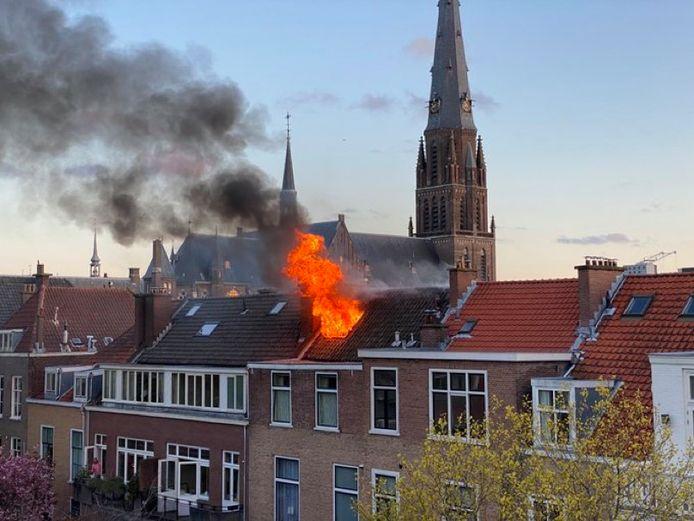 De vlammen slaan uit het dak bij een felle brand in een woning in de Willemstraat in de Haagse binnenstad.