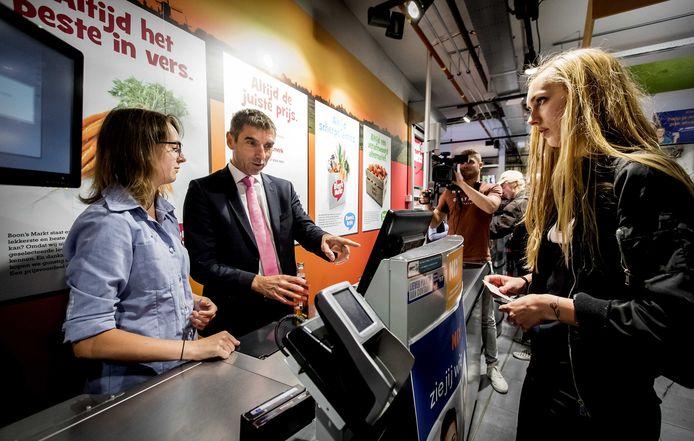 Staatssecretaris Blokhuis controleert de leeftijd van een roker vanachter de kassa van een supermarkt.