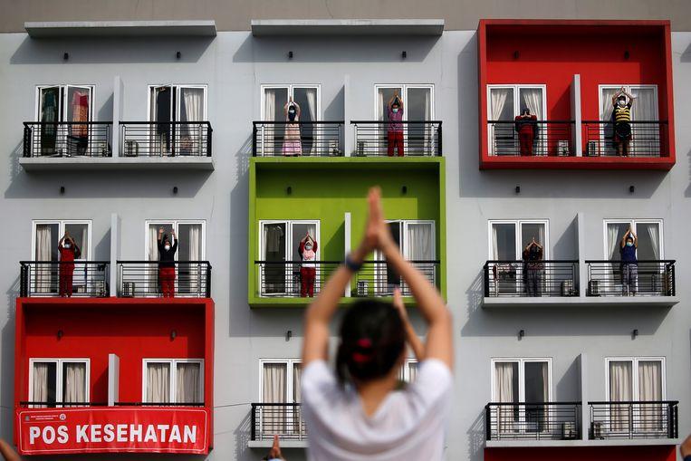Mensen in quarantaine doen oefeningen bij een ander Indonesisch quarantainegebouw in Jakarta: een omgebouwd trainingscentrum.  Beeld REUTERS