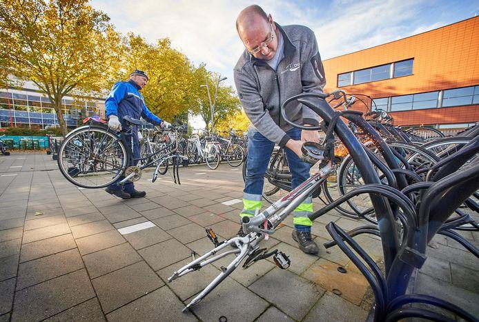 Theo Wels slijpt een fietswrak los van het rek. Toezichthouder Johan van Nimwegen voert een ander exemplaar af.
