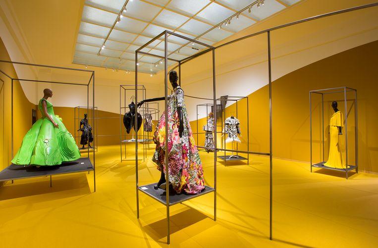 Okergele zalen met japonnen en avondjurken in het Gemeentemuseum Den Haag. Beeld Gemeentemuseum Den Haag/Alice de Groot