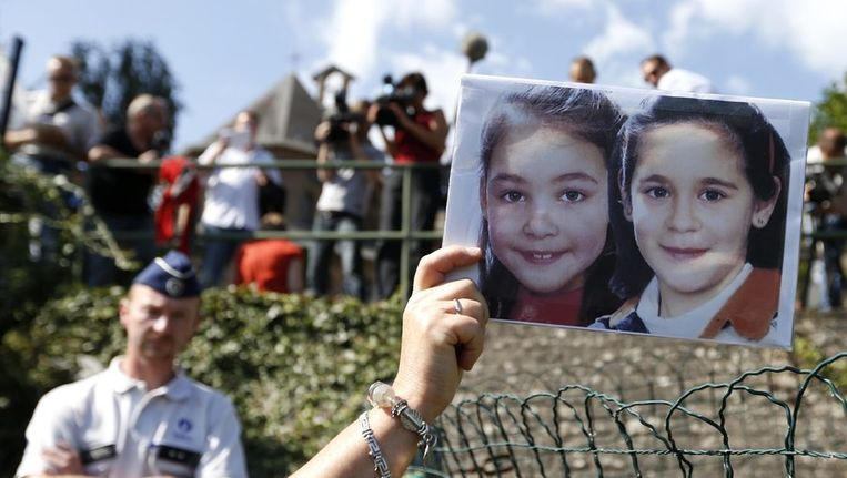 Een demonstrant houdt een portret omhoog van de twee meisjes die zijn omgekomen in de kelder van Dutroux. Ze protesteert bij het klooster waar Dutroux zijn ex-vrouw naartoe is gegaan, nadat zij vervroegd is vrijgelaten. Beeld reuters