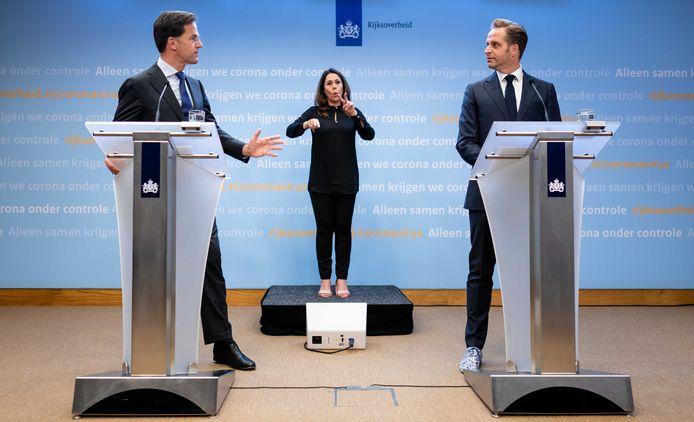 Premier Rutte en minister De Jonge tijdens de laatste persconferentie, mét gebarentolk Irma Sluis. Zij zal morgen ontbreken.