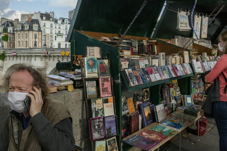 Volgens Jérôme Callais (l.), voorzitter van de Association Culturelle des Bouquinistes de Paris, zijn de verkopen van de boekstalletjes dit jaar met gemiddeld 80 procent ingestort.  Beeld NYT
