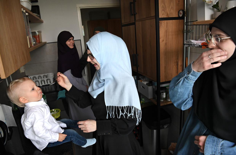 Merima Aljic voert haar zoontje, omringd door haar moeder en zussen. Ze woont nog thuis en zoekt met haar man al acht jaar naar een huurwoning.   Beeld Marcel van den Bergh / de Volkskrant