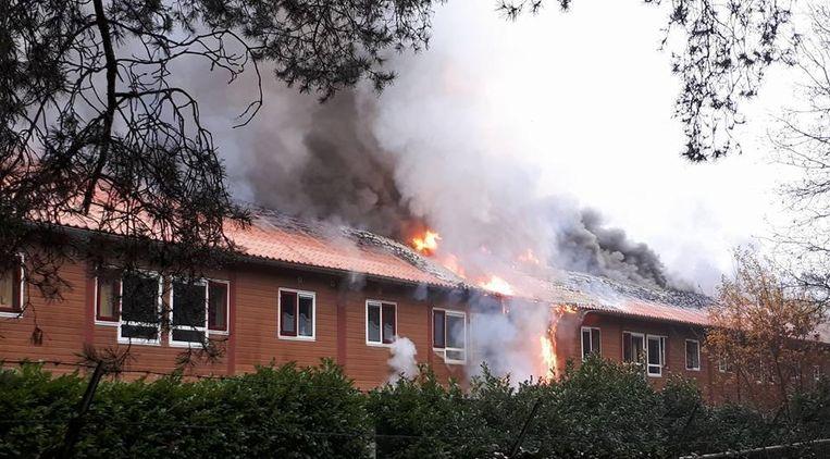 De vlammen slaan hoog door het dak (boven), terwijl er enorme rookpluimen opstijgen uit de bungalows (r.).