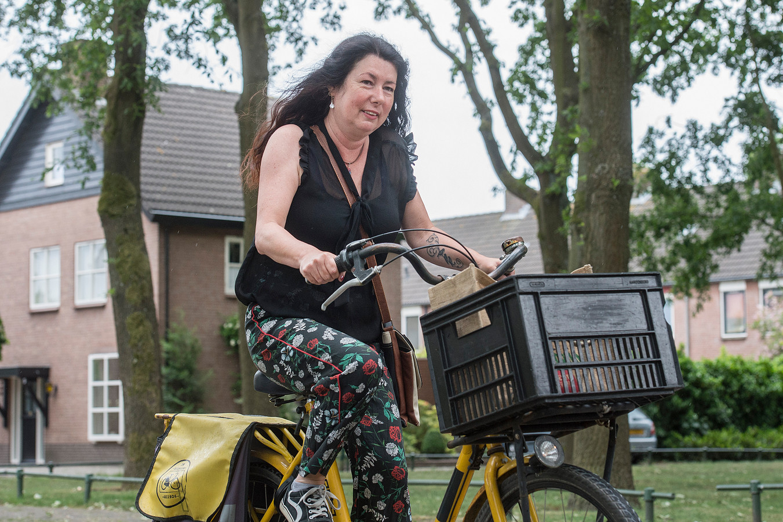 Pix4Profs-Ron Magielse fietskoerier nathalie van daesdonk brengt als vrijwilligster pakketjes rond voor gilze rijen helpt.