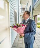 Burgemeester Michel Bezuijen belt met een fraaie bos bloemen aan bij het 60-jarige bruidspaar Kappetein.